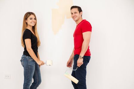 roller brush: Couple of newlyweds decorating and painting their new home and smiling