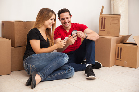moving box: Cute young couple moving to a new house and social networking with their smartphones