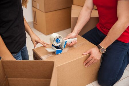 moving out: Closeup of a young couple using a tape gun and packing some boxes before moving out Stock Photo