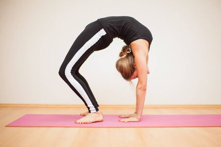 blonde females: Profile view of a blond young flexible woman doing a difficult backbend pose in a yoga studio Stock Photo