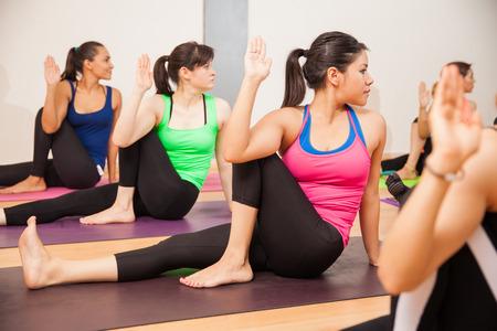 Groep van jonge Spaanse vrouwen die de kronkelende wijze poseren in een yogastudio