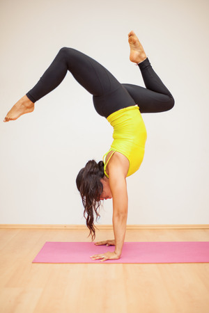 headstand: Young woman doing a headstand with split legs in a yoga studio
