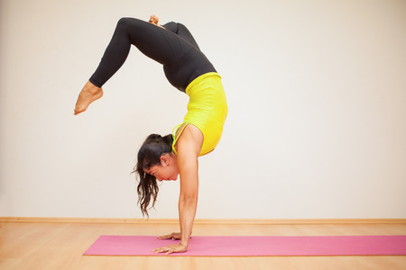 headstand: Pretty brunette doing a headstand with crossed legs during practice in a yoga studio