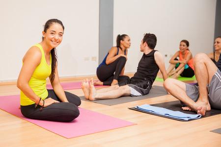 Portret van een mooie jonge yoga-instructeur te ontspannen na het geven van een klasse om een grote groep mensen Stockfoto