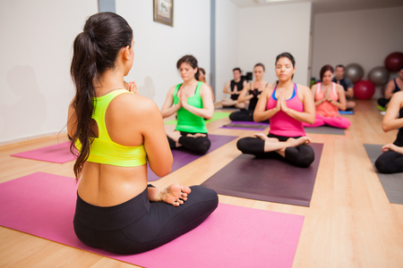 Young female instructor and her students doing some meditation during their yoga class