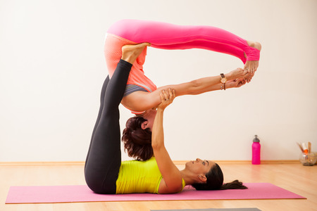 strong women: Two strong young women demonstrating an acrobatic yoga pose in a yoga studio Stock Photo