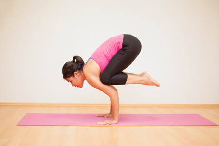 maintaining: Profile view of a young Latin woman practicing a yoga pose and maintaining balance Stock Photo