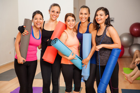 Vijf jonge Hispanic vrouwen lachen en plezier hebben in een yoga studio