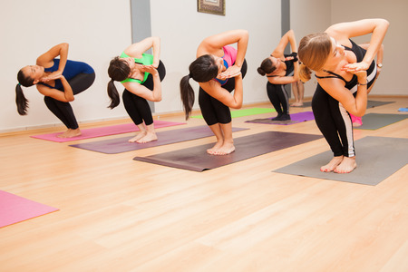 yoga class: Large group of women holding the chair pose during their yoga class. Lots of copy space