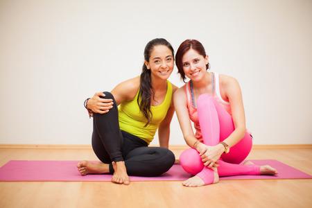 mujer bonita: Retrato de una pareja de amigas disfrutando de su pr�ctica de yoga y sonriente Foto de archivo