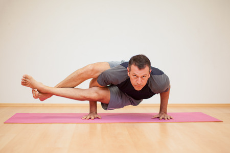 Portrait of a flexible man practicing a few yoga poses in a gym Stock Photo