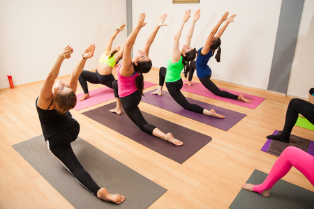 large: Young women and instructor working out together in their yoga class at a gym Stock Photo