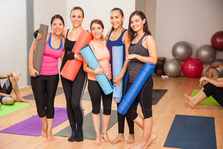 mujer bonita: Retrato de cuerpo entero de un grupo de cinco mujeres con las esteras del ejercicio en un estudio de yoga