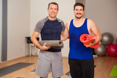 mat: Portrait of a couple of guys carrying exercise mats and smiling in a yoga studio