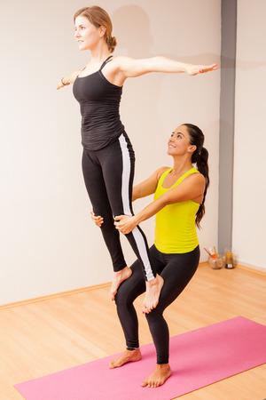 Beautiful young women doing some acrobatic yoga in a yoga studio
