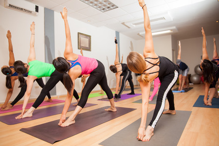 clases: Gran grupo de personas que tienen el triángulo plantean durante una clase de yoga en un gimnasio