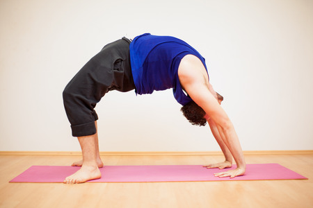 mats: Portrait of a young man doing a backbend pose in a yoga studio against a white background
