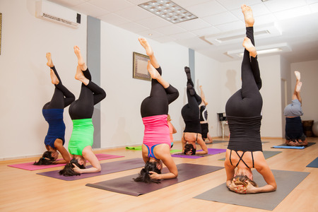headstand: Group of young people doing a headstand during their yoga class Stock Photo