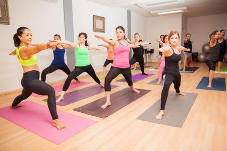Groothoek oog van een vrouwelijke yoga-instructeur onderwijzen van een grote klasse in een sportschool