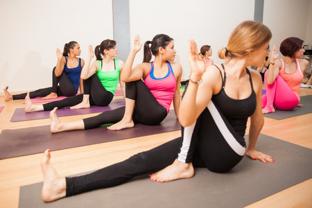 twisting: Large group doing the twisting sage pose in a real yoga class