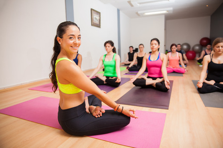instructor: Portrait of a beautiful young yoga instructor smiling during one of her classes