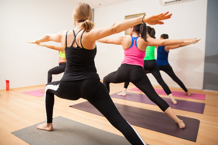 poses: Student point of view of a yoga class following their instructor and doing the warrior pose