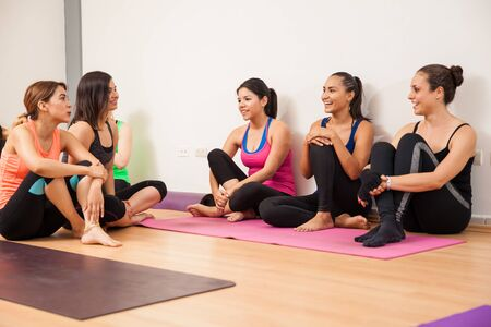 yoga class: Group of women sitting and relaxing after a long yoga class Stock Photo