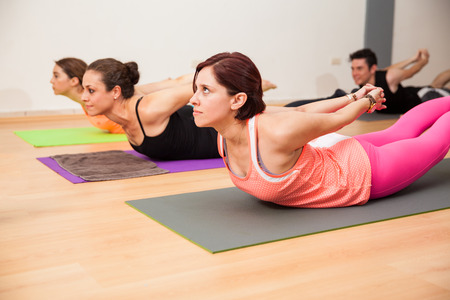 locust: Group of Hispanic people doing the locust pose with interlaced hands in a yoga studio Stock Photo