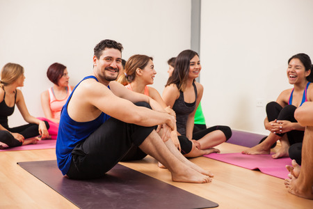 men talking: Portrait of a young man resting and socializing after an intensive yoga class Stock Photo