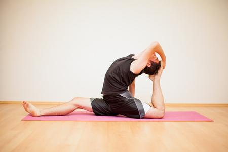Flexible junge Mann, der ein paar Yoga Posen in einem Fitness-Studio Standard-Bild - 42872237