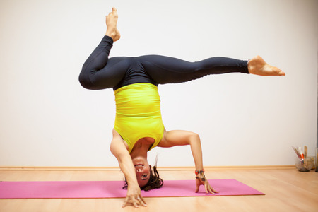 headstand: Beautiful strong woman doing a headstand with a leg split in a yoga studio