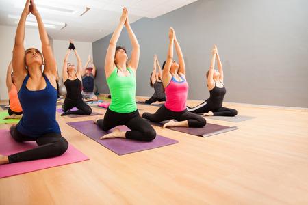 clases: Retrato de un gran grupo de personas que hacen una estocada baja pose durante una clase de yoga de bienes Foto de archivo
