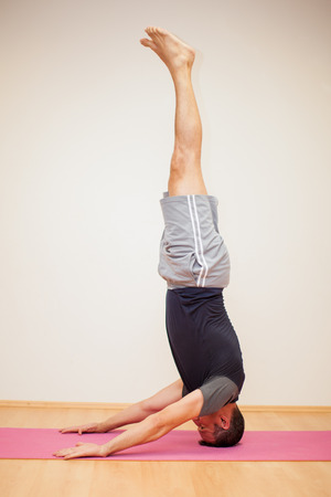 headstand: Profile view of a man doing a headstand and maintaining balance in a yoga studio