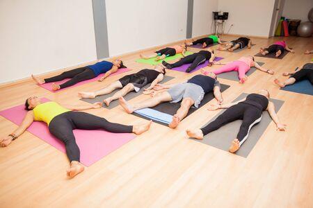 Brede hoek weergave van een grote groep mensen in de savasana poseren in een yogastudio