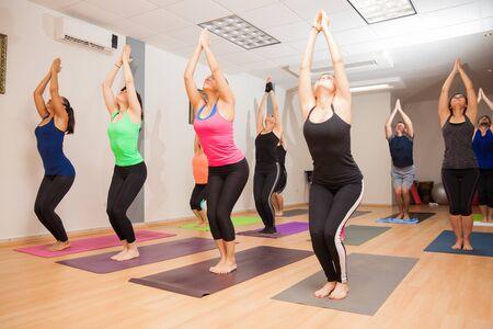 Brede hoek weergave van een grote groep van mensen die een stoel tijdens een echte yogales pose