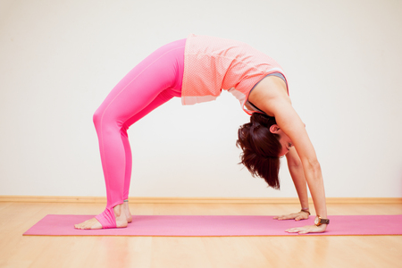 yoga pose: Young woman practicing a backbend yoga pose in a yoga studio