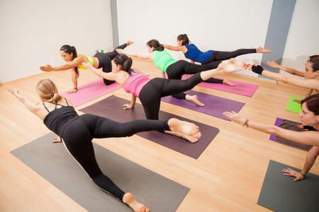 Grote groep van jonge Latijnse vrouwen op handen en voeten en arm en been uitgebreid in een yoga-studio