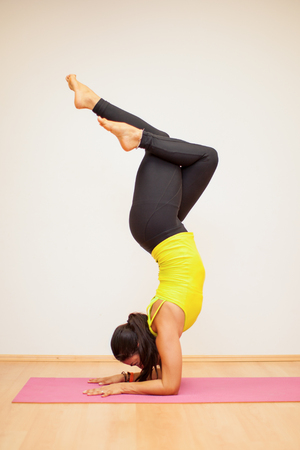 headstand: Young athletic brunette doing a cross-legged headstand in a yoga studio