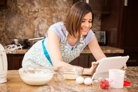 Mignon jeune femme utilisant un ordinateur tablette et les réseaux sociaux pendant la cuisson dans la cuisine