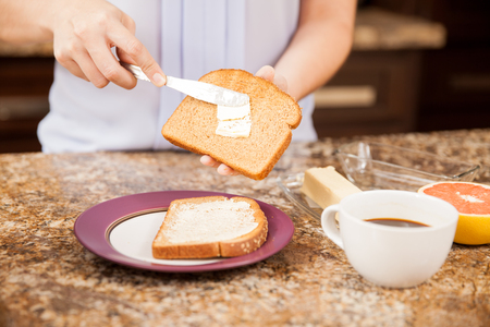 woman knife: Closeup of a woman adding some butter to her toast and having some coffee and fruit to go with it Stock Photo