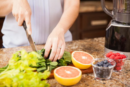 Closeup of a young woman cutting some fruit and vegetables to make herself a healthy juice at home