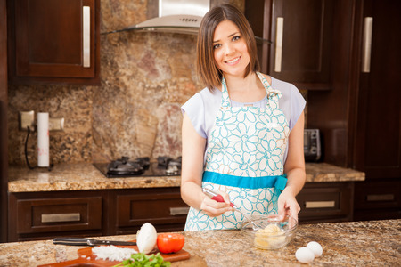 beating: Beautiful young Hispanic woman beating some eggs in a bowl and making an omelette Stock Photo