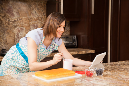 young add: Good looking young woman reading a cake recipe online and getting ready to add some frosting to her cake
