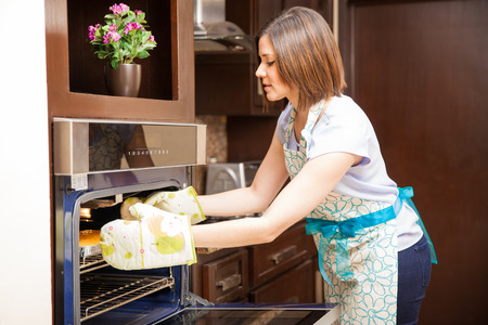 baking oven: Attractive young brunette using oven mitts to get a cake out of the oven