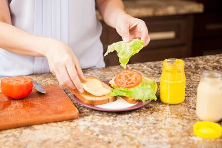 adult sandwich: Closeup of the hands of young woman preparing a sandwich at home Stock Photo