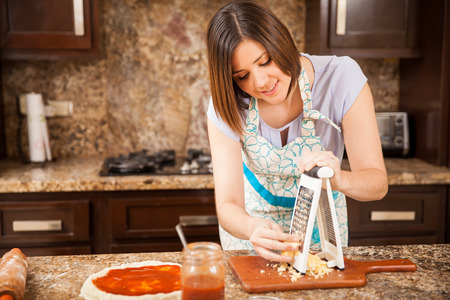 Attractive brunette in an apron grating some cheese and adding it to a pizza in the kitchen Stock Photo
