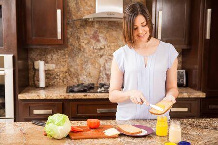 bocadillo: Bastante joven mujer poniendo un poco de mostaza en un pan y preparar un bocadillo para el almuerzo