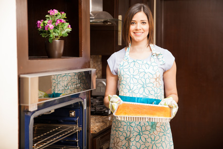 Portrait of a beautiful Hispanic young woman with an apron and oven mitts holding a cake next to the oven and smiling Imagens