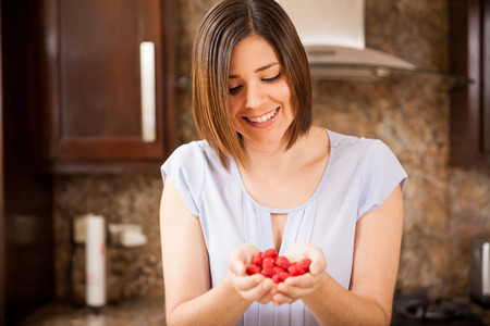 raspberries: Cute young brunette holding a bunch of raspberries in her hands and smiling Stock Photo
