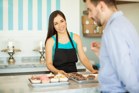 woman shop: Portrait of a cute young woman showing a few trays of cupcakes to a customer in a cake shop